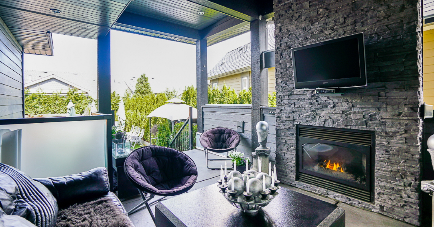 Outdoor covered patio living room with fireplace and and TV designed and built by 360 Home Renovations