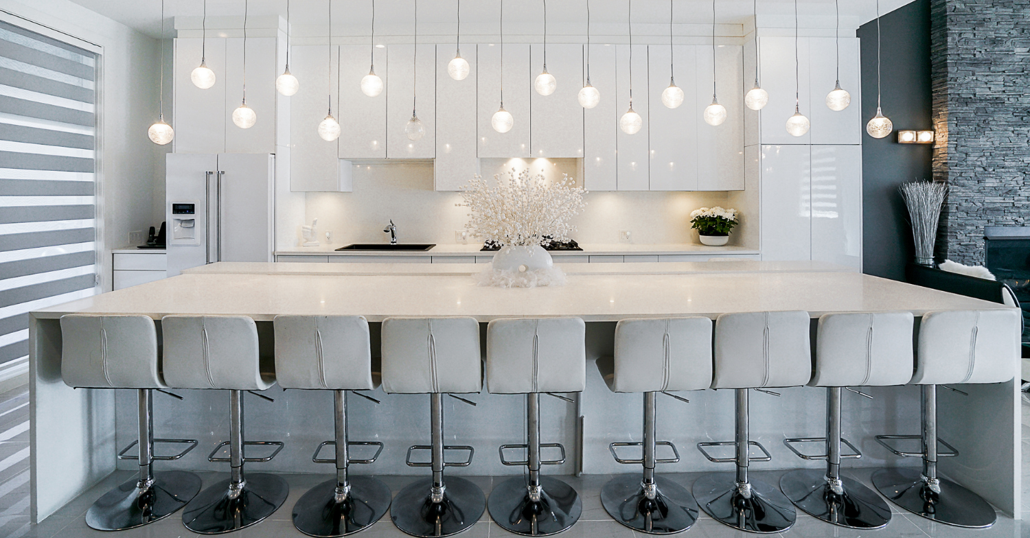 Kitchen remodel with clean lines, white cabinetry, island seating and statement light fixtures; design and build by 360 Home Renovations.